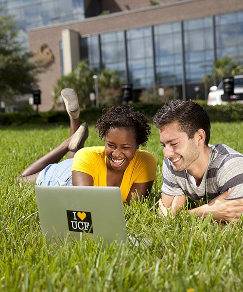 Two students in grass outside Career Services